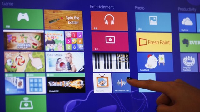 An attendant demonstrates the Microsoft Windows 8 operating system