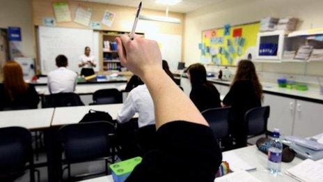 A pupil raising their arm in class