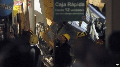 Rescuers work amid debris inside a supermarket where the roof collapsed in Neuquen