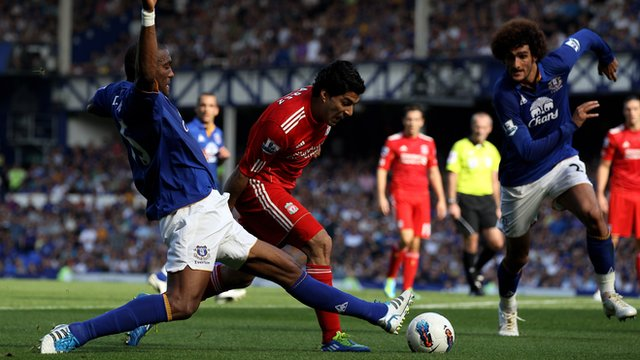 Everton and Liverpool battle for possession