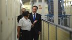 Britain's Prime Minister David Cameron is escorted around C wing by prison officer Margaret Vaughan during his visit to Wormwood Scrubs Prison