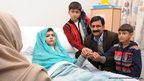 Malala Yousafzai sits up in her hospital bed with her father Ziauddin and her two younger brothers in Birmingham