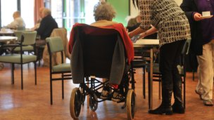 An old lady sits at a table