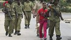 Zanzibari police detain a protester who is holding his shoes -  Friday 19 October 2012