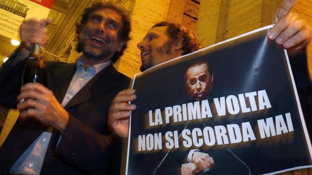 "People hold a picture of Italy""s former PM Berlusconi with words that read ""You Never Forget Your First Time"" as they celebrate after Berlusconi was sentenced to jail for tax fraud in downtown Rome"