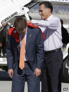 "Romney signs a t-shirt on the back of his ""body man"" Garrett Jackson"