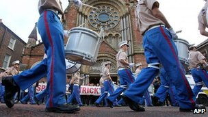 loyalist band marches past protesters