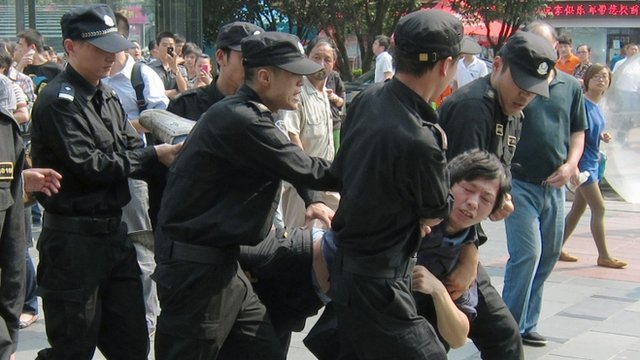 Protester carried by riot police