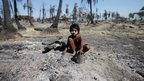 Girl collects metal from rubble in Pauktaw township, burnt in recent violence - 27 October