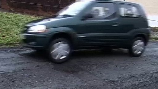 Car driving over a pothole