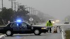 Police set up road block as water from Hurricane Sandy cover road in Nag's Head, North Carolina