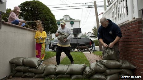 Families install a wall of sandbags to protect their basement in Queens, New York, October 28