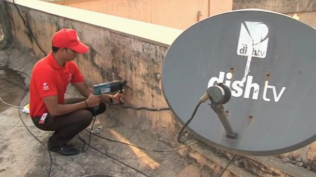Engineer installing a satellite dish in India