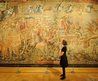 Curator Kate Heard views the tapestry The Triumph of Time over Fame