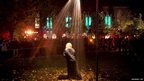 A performer stands in a street light shower