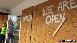"Woman walks into a boarded-up store. Sign says ""WE ARE OPEN."""
