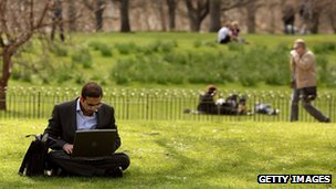 Man uses laptop in park