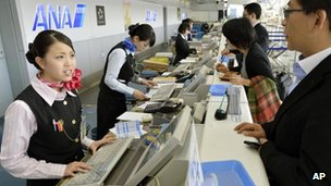 Employees deal with passengers at the counter at Sendai Airport in Sendai, northern Japan after flights in and out of the airport were cancelled 30 October, 2012