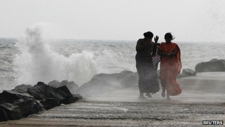 A woman covers her face as waves hit the promenade at the fishing harbour in the southern Indian city of Chennai October 29, 2012
