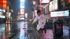 A woman in a dressing gown and wellington boots jumping in Times Square