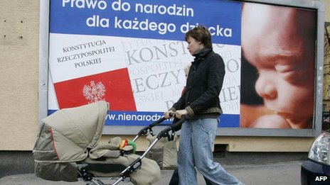 "A mother with a child passes a poster with inscription ""Right to be born for every child"" in Warsaw 15 March 2007"