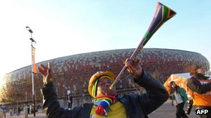 A football fan blows a vuvuzela trumpet outside Soccer City stadium in Johannesburg on 20 June 2010 just hours before the South Africa 2010 World Cup match between Brazil and Ivory Coast