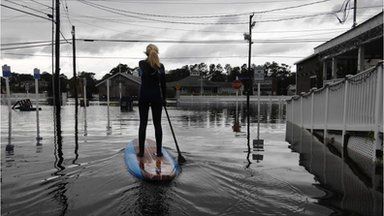 Woman paddle-boards down flooded street in Bethany Beach, Delaware (30 Oct)
