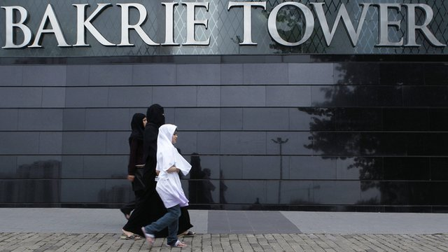 Women walk in front of the Bakrie Tower in Jakarta