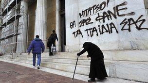 Lady begs outside Bank of Greece