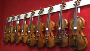 Violins hanging on wall ready to be sold at auction