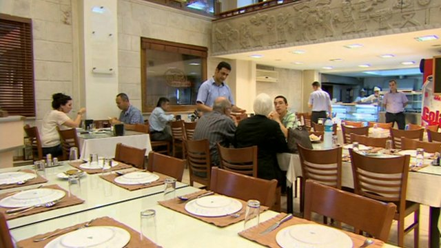 Customers order in a half-empty Turkish restaurant