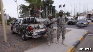 Two soldiers stand guard beside an armed pick-up truck outside the Libyan General National Congress