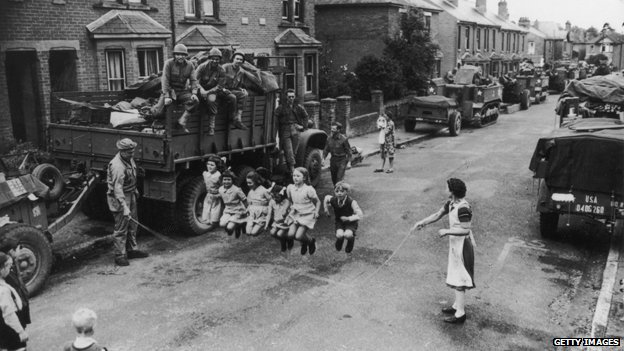 A US soldier helps British children with their skipping