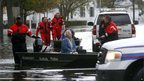 Elaine Belviso is moved by boat from her flooded home in Suffolk County, Long Island