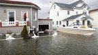A resident of  Lindenhurst in New York state inspects damage to his house and the boat moored in his driveway