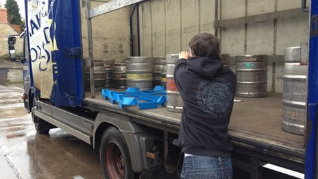 A lorry being unloaded with kegs of beer.