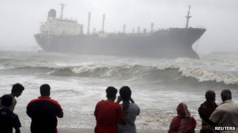 Onlookers watch ship Pratibha Cauvery, which ran aground allegedly due to strong winds, on the bay of Bengal coast, in the southern Indian city of Chennai, October 31, 2012