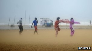 Women shield their faces during strong winds at Marina beach in the southern Indian city of Chennai October 31, 2012