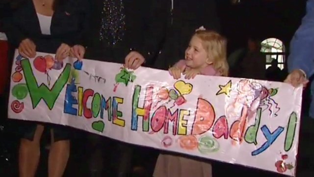 A girl holds up a banner welcoming home her daddy