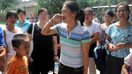 A group of upset Chinese migrant workers gather outside an &#039;unlicensed&#039; school, after they arrived to register their children for the new semester but were informed that the school will be shutdown, in the suburbs of Beijing on August 10, 2010