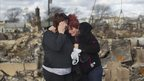 Neighbours embrace at the wreckage of their homes in Breezy Point, New York 31 October 2012
