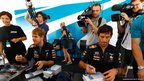 Sebastian Vettel and his Red Bull Racing team mate Mark Webber sign autographs