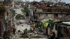 People walk on a street littered with debris after Hurricane Sandy hit Santiago de Cuba
