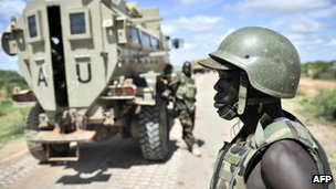 A Ugandan soldier in Somalia watches a convoy depart