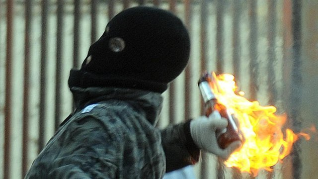 Man in balaclava with petrol bomb