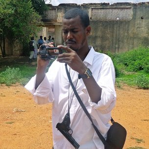 Somali journalist Abdukadir Hassan Abdirahman, who carries a gun, films a scene on 23 October in Mogadishu