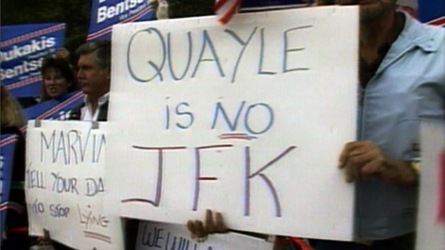 Person holds sign against Dan Quayle