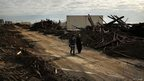 People walk through the heavily damaged Rockaway neighbourhood, in Queens where a large section of the iconic boardwalk was washed away on November 2, 2012 in New York, United States