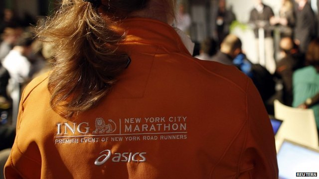 Worker wearing an official jacket listens as the New York Road Runners cancel the 2012 ING Marathon due to Hurricane Sandy