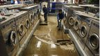 Staff in a laundromat sweep out mud and water, Coney Island, New York